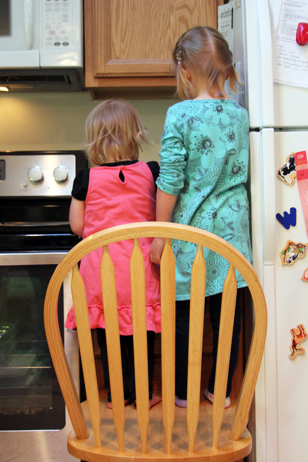 girls standing on chair making food