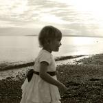 little girl in dress at beach