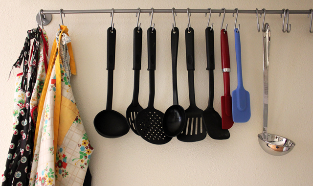 aprons and kitchen utensils hanging on wall